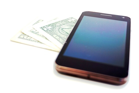 The black cell phone - a communicator on banknotes of U S D and a white-gray background photo
