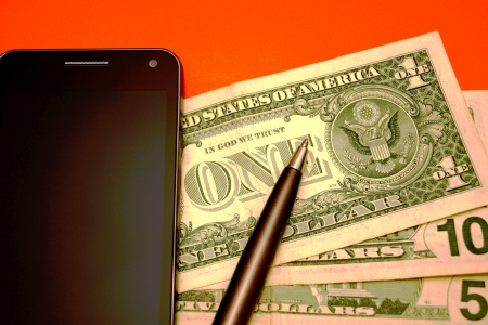 The mobile phone, the American banknotes and pen on a red background photo