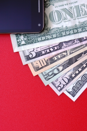 The mobile phone, the American banknotes on a red background photo