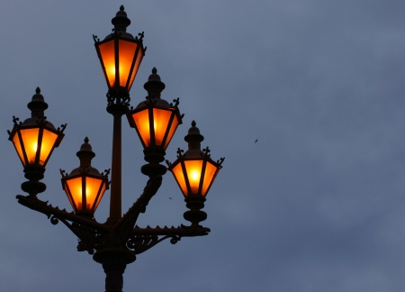 Ancient lamps on a column shine the night sky photo