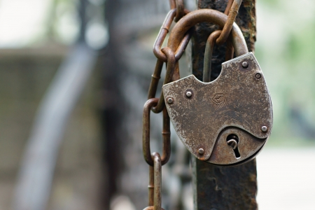weighs: The old lock through a chain weighs on a column of an iron fencing Stock Photo