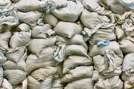 Huge heap of bags from fabric with dry leaves and garbage photo