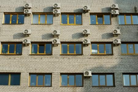 古いれんが造りの壁に窓やエアコンの数が多い建物のファサード