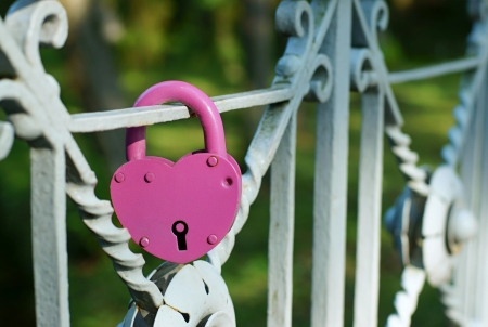 fidelity: The lock of red color closed on the bridge as a symbol of love, fidelity and devotion Stock Photo