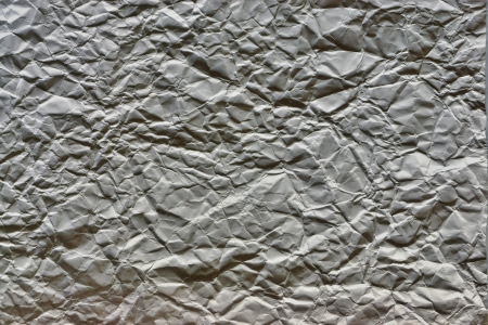 The crumpled sheet of paper of gray graphitic color for a background and an abstract surface, for the text photo