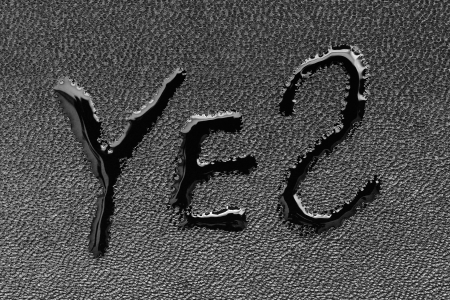 The word YES on black skin is written by a liquid closeup photo