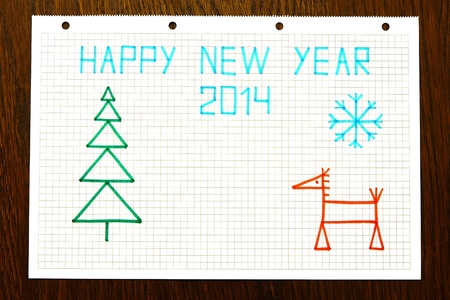 Childrens drawing with an inscription Happy New year 2014 on a notepad leaf in a cage, place for the text photo