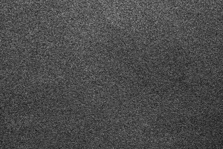 Fine-grained texture of a black abrasive material for wallpaper and for abstract backgrounds