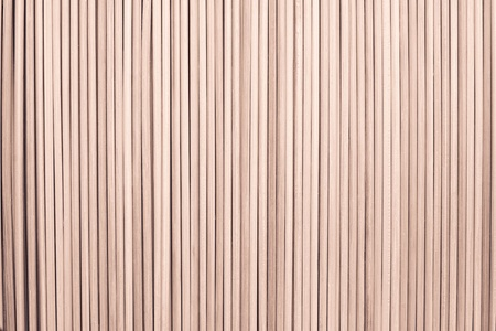 laths: the abstract textured background from wooden cylindrical sticks of brown color Stock Photo