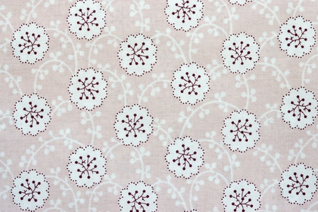 florets: the textured background of cotton fabric of pink color with a pattern from abstract florets