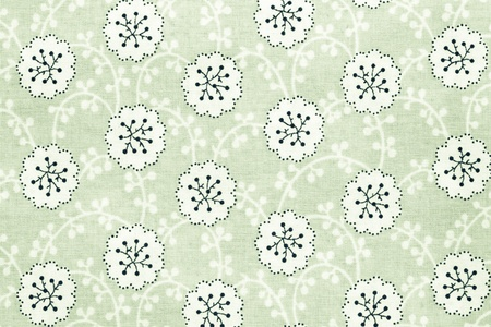 florets: the textured background of cotton fabric of green color with a pattern from abstract florets