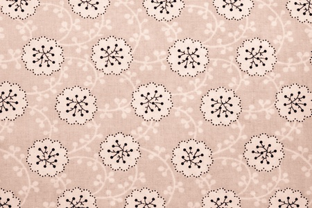 florets: the textured background of cotton fabric of terracotta color with a pattern from abstract florets