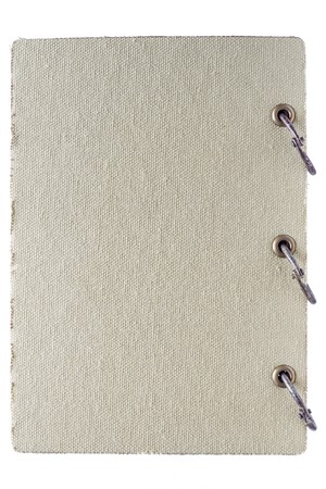 the closed old notebook with a textile cover and metal binding rings isolated on a white background closeup photo