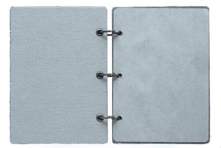 open notebook on a white background with a cover from fabric and with paper pages of silvery color photo
