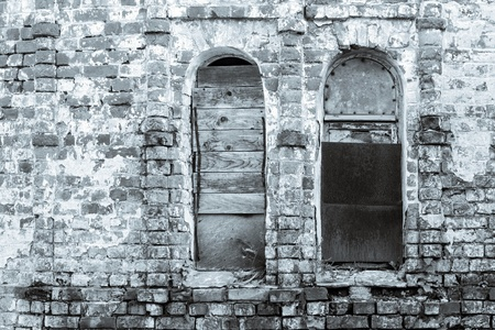 niches: abstract fragment of monochrome tone of an old brick wall with window niches Stock Photo