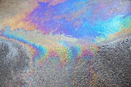 the abstract textured pattern of an oil or petrol slick on wet asphalt of the road