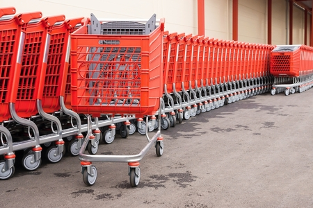 household goods: red plastic baskets-carts on wheels for warehousing of food and household goods upon purchase in shops and in markets