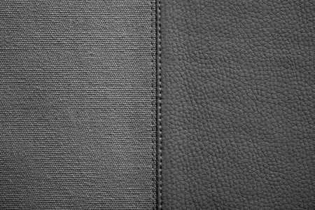 fabric textures: the stitched combination of two textures of black color from rough fabric and an imitation leather for abstract backgrounds