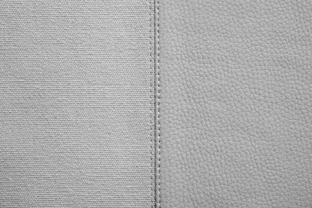 fabric textures: the stitched combination of two textures of gray color from rough fabric and an imitation leather for abstract and for festive backgrounds