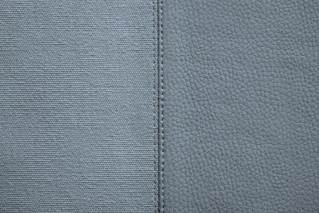 fabric textures: the stitched combination of two textures of silvery color from rough fabric and an imitation leather for abstract and for festive backgrounds