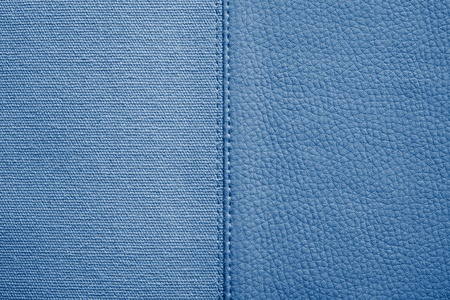 fabric textures: the stitched combination of two textures of blue color from rough fabric and an imitation leather for abstract and for festive backgrounds