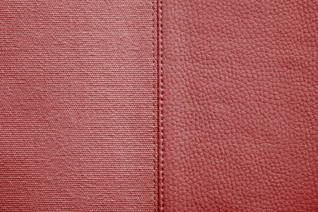 fabric textures: the stitched combination of two textures of red color from rough fabric and an imitation leather for abstract and for festive backgrounds
