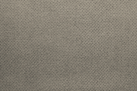 seamy: texture of leather fabric with a wrong side for empty backgrounds of beige color with the punched openings