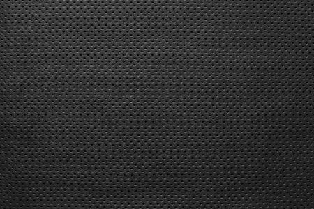 パンチの開口部を持つ黒い色の純粋な背景の外側の革生地のテクスチャ