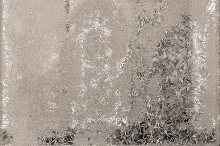 silvery: abstract textural winter patterns on the frozen glass of silvery beige color