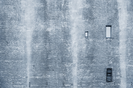 silvery: big brick wall of the old building of silvery color with the damaged plaster and with small windows
