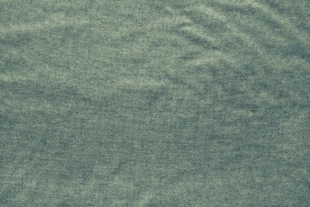 gunny: rough texture of the wavy crumpled fabric of green color with a dense mesh interlacing of threads as gunny for empty and pure backgrounds Stock Photo