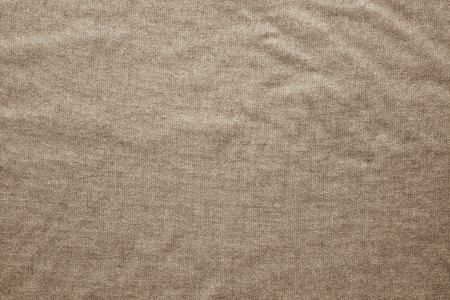 gunny: rough texture of the wavy crumpled fabric of sepia color with a dense mesh interlacing of threads as gunny for empty and pure backgrounds
