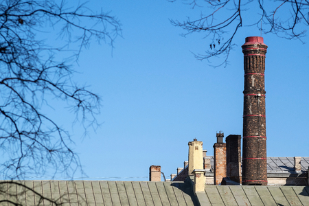 flue: high ancient flue without smoke from an old red brick on an iron roof against the blue sky behind small boughs of trees Stock Photo