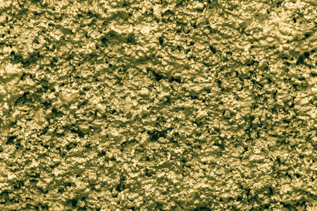 bumpy: bumpy texture of a rough shapeless shining surface of a wall of golden color for empty abstract backgrounds