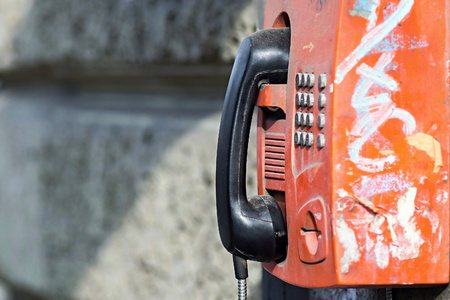 payphone: the old red payphone with a black receiver is fixed on a stone wall with a blank space for the text