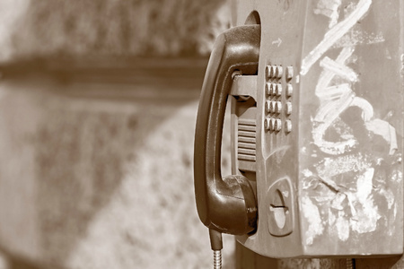 payphone: the digital photo in tone sepia the old payphone with receiver is fixed on a gray stone wall with a blank space for the text