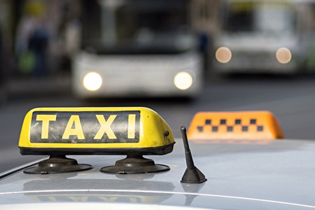 vague: automobile emblem and sign of a taxi against city streets with the vague image of buses and the included headlights