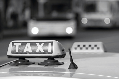 vague: automobile emblem and sign of a taxi against city streets with the vague image of buses and the included headlights in monochrome tones Stock Photo