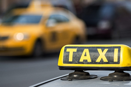 vague: The image of a sign of a taxi closeup on an indistinct of the car of a taxi of yellow color Stock Photo