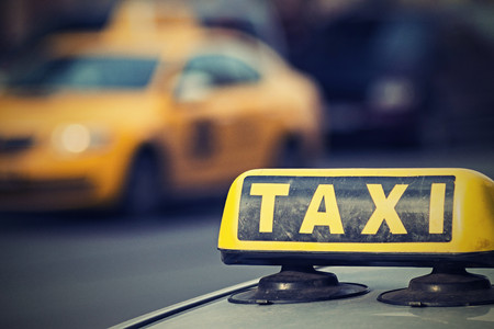 The image of a sign of a taxi closeup on an indistinct of the car of a taxi of yellow color with digital retro effect