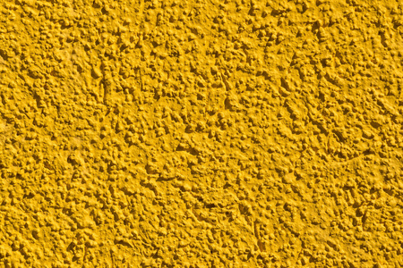 grained: the rough grained surface is plastered in bright yellow color for the textured empty and pure backgrounds Stock Photo