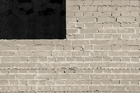 window opening: gray brick wall under construction with a window opening for the abstract textured backgrounds Stock Photo