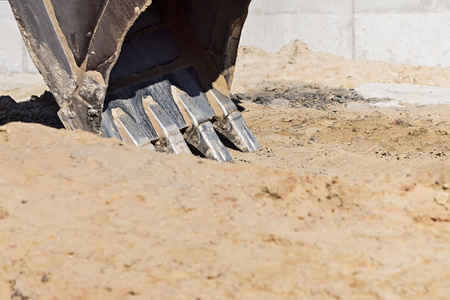 steel bucket: part of an old bucket with steel teeth for the excavator on a sand background