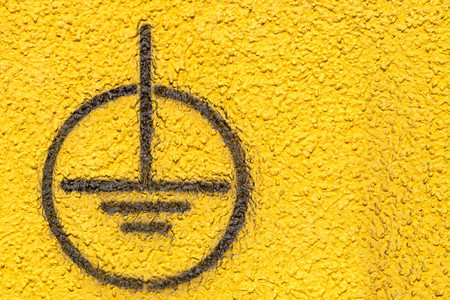 grounding: the image of a black sign of grounding on the yellow rough plastered wall for industrial backgrounds Stock Photo