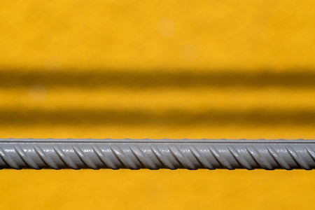 abstractions: the gray textured fittings rod on an indistinct background of a yellow wall with shadow strips for industrial abstractions Stock Photo