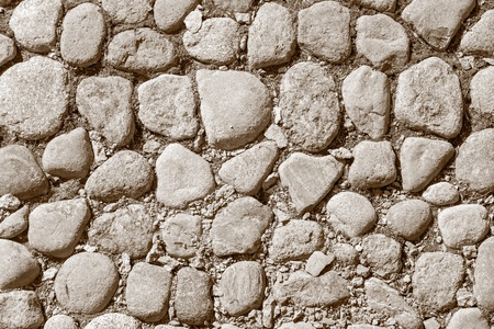 bumpy: old pavement from a natural stone of sepia color for the textured abstract background