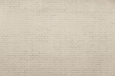 the pale beige textured surface of a brick wall for empty and pure backgrounds