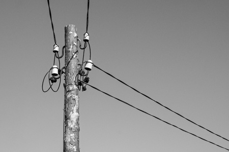 insulators: industrial a retro scenery from an old wooden column with electric wires and a cable on ceramic insulators of monochrome gray color