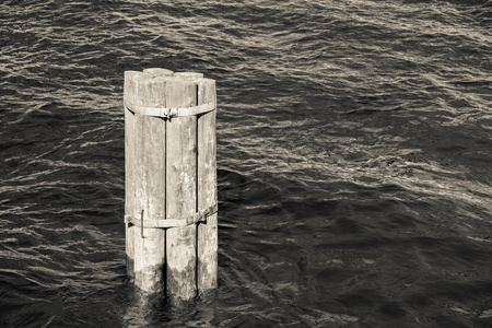 bridge footing: monochrome tone the old wooden column for the bridge footing alone sticks out of water Stock Photo