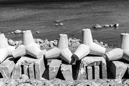 breakwaters: strengthening from big concrete breakwaters on the bank of the sea gulf closeup in gray tones Stock Photo